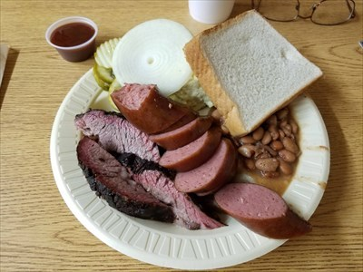 Sliced brisket, sausage, homemade potato salad, and beans.