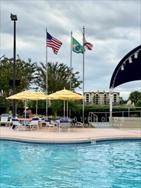 Six flags flank a fabric covered bandstand to the west of a Waters Edge swimming pool at Orange Lake Resort in Kissimmee, Florida. The flags of the United States, Brazil and Florida fly south of the stage.