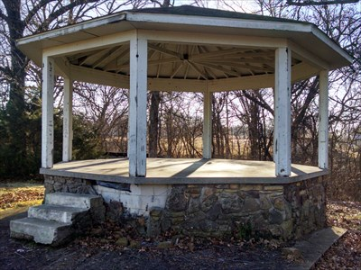 Gazebo at the Seligman City Park, by MountainWoods.  This photo shows some of the damage to the stone façade caused by the improperly-placed geocache, whose coordinates brought you to just to where this damage is located, just right of the steps.  I do not know where the geocache was because it was long gone when I tried to find it in 2012.  Just touching the stone caused some of it to fall down, unfortunately. :(