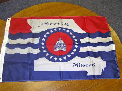 The colorful flag shows the outline of the state, the central capitol dome, and the waters of the Missouri in a colorful display of red, white and blue.