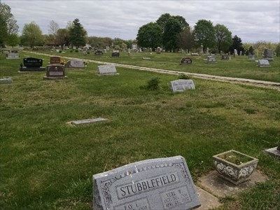 100 - Fay Stubblefield, by MountainWoods. Context photo looking toward the arched entrance to the cemetery.