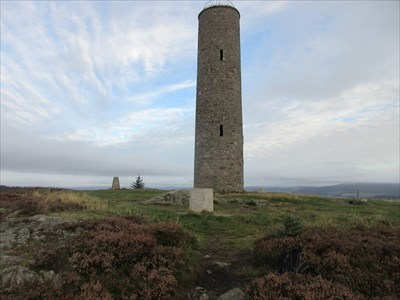 View of the tower, with the south indicator in the foreground, the north indicator to the right of the tower, and the trig pillar to the left.