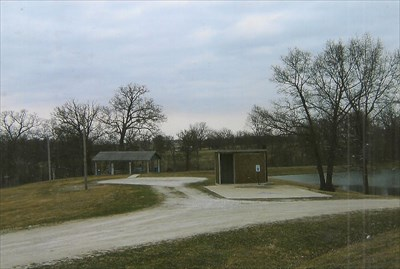 restroom, two camp hookup sites and pavilion with pond in background