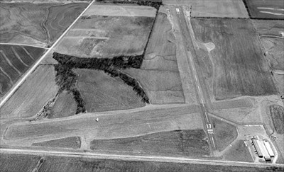 The only photo which has been located showing an aircraft at Pershing Memorial Airport  was a 1997 USGS aerial view looking south, which showed a single-engine aircraft headed west on the grass crosswind runway.  It depicted Pershing to have a single paved Runway 17/35, as well as a grass crosswind runway. A ramp & a cluster of hangars was located on the northwest corner of the field.