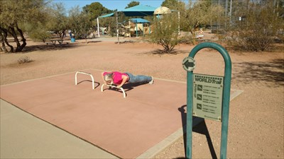 She is doing a comfort push-up.  She holds her hands at a comfortable distance apart, then does a push up, holding for a count of 2 on each one.