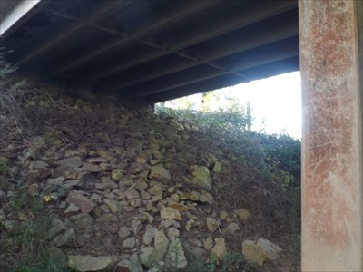 Under view, showing the rocky abutment and the concrete stringers.
