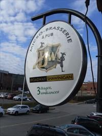 L'Enseigne du Pub près de la rue et du stationnement.Ensign's Pub near the street and parking.