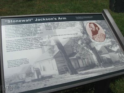 A historical sign is near the grave.