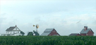 Wessels Living History Farm farmstead as seen from Highway 81.  Windmill is prominent among the buildings.
