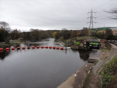 The orange boom to stop boats can be seen. The entrance to the lock on the Huddersfield Canal is to the right of the boom under the footbridge.