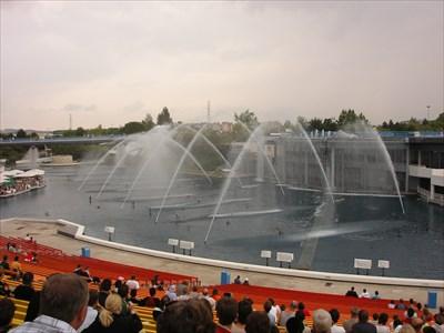Un immense bassin entouré de gradins avec spectacle et jeux d
