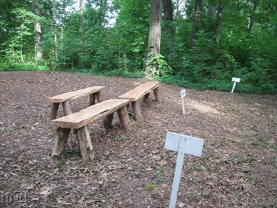 Signs mark the east and west walls. These benches are made of logs, but the original pews were cushioned.