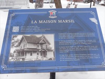Panneau de la Maison Marcil fixé a une plaque et un poteau de métal au sol.  Marcil panel of the House has a fixed plate and a metal pole to the ground.