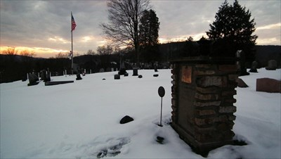 Matthew Young's grave near sunset with the Veteran's Memorial in Background.