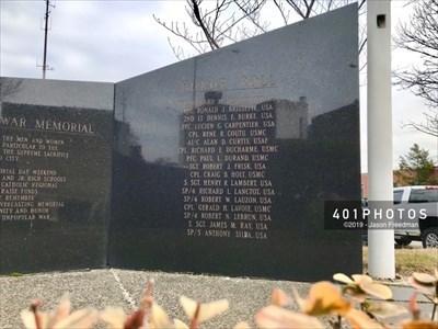 The fourth and final element is a cenotaph with the names of 17 Woonsocket service members who died during the Vietnam War: SGT. RICHARD M. BEAUREGARD, USA - PFC. RONALD J. BRISSETTE, USA - 2ND LT. DENNIS E. BURKE, USA - PFC. LUCIEN G. CARPENTIER, USA - CPL. RENE R. COUTU, USMC - A1/C. ALAN D. CURTIS, USAF - CPL. RICHARD E. DUCHARME, USMC - PFC. PAUL L. DURAND, USMC - SGT. ROBERT J. FRISK, USA - CPL. CRAIG B. HOLT, USMC - S. SGT. HENRY R. LAMBERT, USA - SP/4 RICHARD L. LANCTOT, USA - SP/4 ROBERT W. LAUZON, USA - CPL. GERALD H. LAVOIE, USMC - SP/4 ROBERT N. LEBRUN, USA - S. SGT. JAMES M. RAY, USA - SP/5 ANTHONY SILBA or SILVA (ambiguous engraving correction), USA