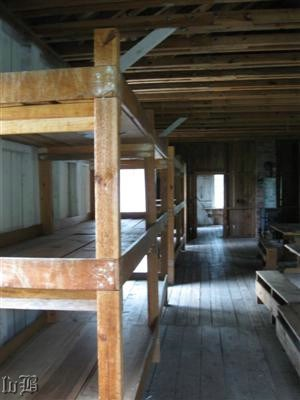 Looking down the length of the barracks for enlisted men. The bunks were 3 high on both sides of walls with tables down the middle.