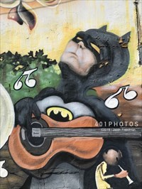 DETAIL: Batman grooves on an acoustic guitar