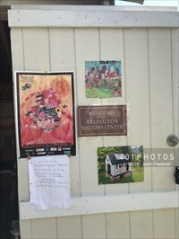 """The inside of the open front door is adorned with a promotional poster for the 2019 Arlington International Film Festival (November 7 - 10) at the Capitol Theatre and a hand-written list of local attractions """"Open on Saturday"""" (eg. Jason Russell House, Cyrus Dallin Museum, Old Schwamb Mill) and """"Open on Sunday"""" (eg. Jason Russell House, Cyrus Dallin Museum)"""