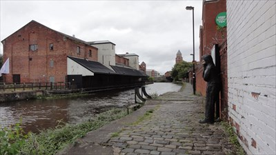 Warehouses and loading wharves can be seen on the other side of the canal.