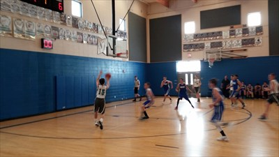 My stepson shooting a basket inside the gym during an AAU basketball tournament game.