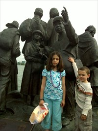 The kids posing with the statue while attending the Hoedown today.