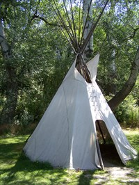 A tipi nestled in the trees at Whitman Mission near the Great Grave