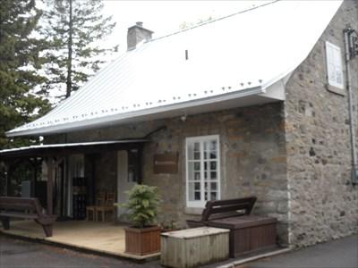 Photo du côté arrière de la maison et sa petite galerie.  Photo of the back side of the house and its small gallery.