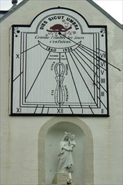 The Ursulines sundial on the wall above an alcove with a stature of the Blessed Virgin Mary