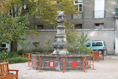 Une fontaine en bien mauvais état, qui a perdu sa partie haute mais qui j