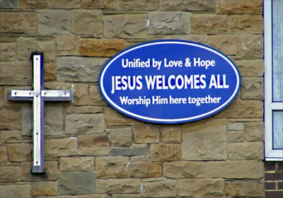 Sign and cross on the front of the church.