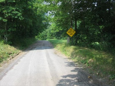 Looking west, the stone is at the END GARRETT COUNTY MAINT sign on the right