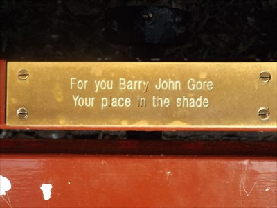 On a brown slat bench, overlooking the Opera House, and the Harbour Bridge.