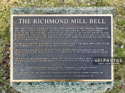 Informational plaque mounted on top of a concrete plinth beside the bell tower