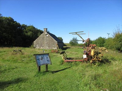 The marker, with Guildymuir in the background along with the old farming equipment.