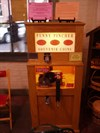 This penny smasher sits in the northeast section of the market house, by the bakery near the door.