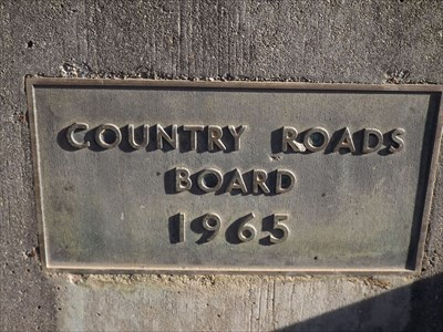The embedded bronze plaque, in the concrete parapet at the southern end, western side of the Great Alpine Road. Built by: Country Roads Board (Victoria) - 1965