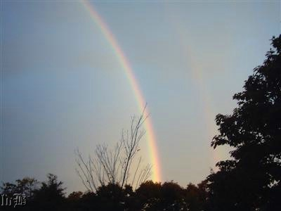 A double rainbow in an early morning sky.