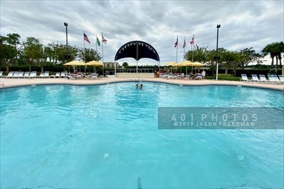 Six flags flank a fabric covered bandstand to the west of a Waters Edge swimming pool at Orange Lake Resort in Kissimmee, Florida. The flags of the United States, Brazil, Florida, Puerto Rico, United Kingdom and Canada fly by the stage.