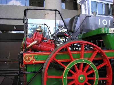 The locomotive engineer sits adjacent to the cylinders of the steam engine.