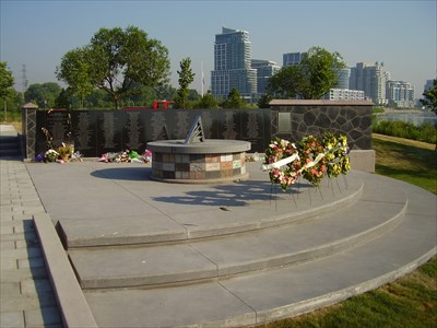 The dial is in front of the wall with the names of the victims. The Toronto skyline is in the background.