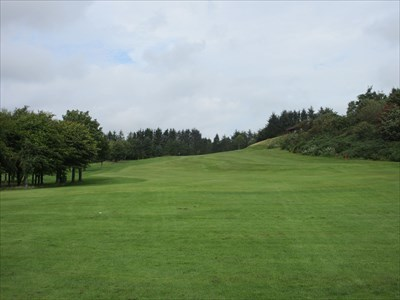 The final hole from the tee. It is a lengthy par 4 (par 5 off the white tees) which runs along the side of the hill. The clubhouse lies up the hill to the right.
