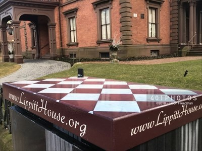 A decorative wrap customizes the utility box on the south side of Angell Street near the intersection with Hope Street to celebrate and promote the Lippitt House Museum, beside which it stands in Providence, Rhode Island. A checkered pattern tops the design.
