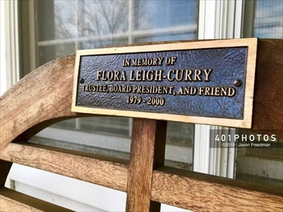 A memorial bench for Flora Leigh-Curry is beside the main entryway to the Greenville Public Library in Rhode Island.