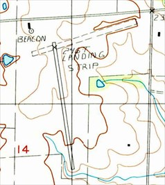 """The 1984 USGS topo map depicted a single paved northwest/southeast runway, and an unpaved northeast/southwest runway, labeled simply as """"Landing Strip"""".  A beacon was depicted on the northwest side."""