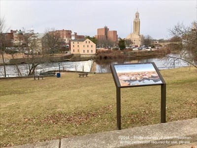The marker on Broadway and Slater Mill as seen from across the Blackstone River.