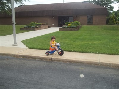 Mikey riding his bigwheel out front of the Building.