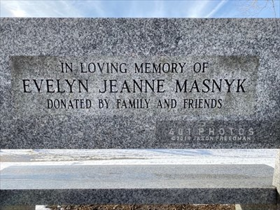 A bench made from polished gray granite and dedicated to Evelyn Jeanne Masnyk can be found in Manville Memorial Park of Lincoln, Rhode Island, midway down a small slope covered by a line of mature trees between a picnic pavilion and a playground.