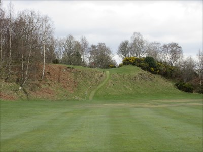 The second shot at the 8th. The green sits over 30 feet high on top of a grassy, stony cliff.