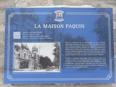 Panneau de La Maison Paquin fixé sur le mur entre le magasin et la maison.   Maison Paquin panel mounted on the wall between the shop and home.