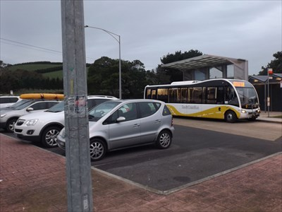 A coach dropping off some customers. Nice sized car park.